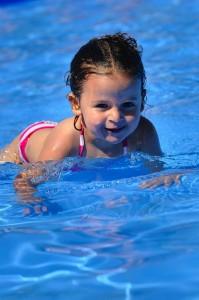 Petite fille en train de nager dans la piscine en plein soleil