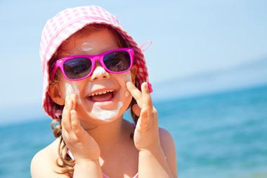 Petite fille protection solaire visage