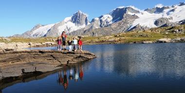Famille au bord d'un lac de montagne Photo : Michele Giroud