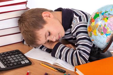Enfant fatigué endormi sur ses devoirs