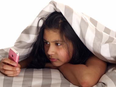 Ado au lit avec son téléphone portable