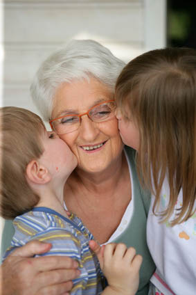 Enfants embrassant une femme senior souriante sur la joue