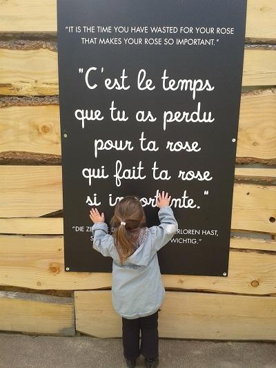 Lilou devant panneau dans le labyrinthe du Parc du Petit Prince