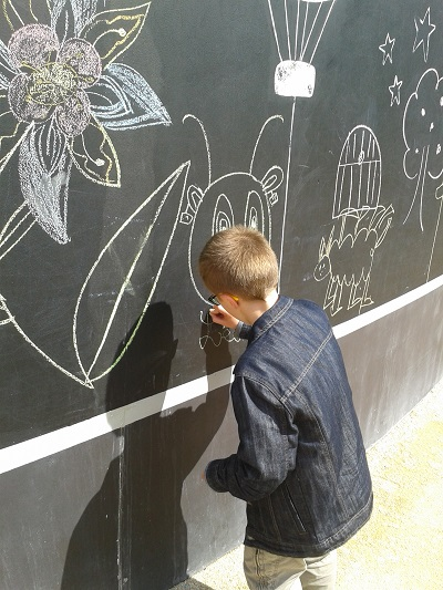 Leo dessine à la craie sur mur dédié au Parc du Petit Prince