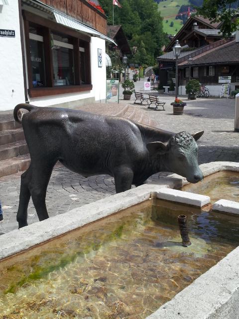 Fontaine avec sculpture vache au centre de Gstaad