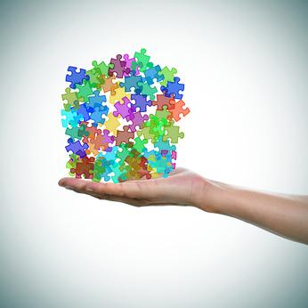 homme tient dans la main des pièces de puzzles comme symboles de l'autisme