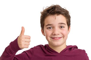Jeune garçon souriant signifiant avec le pouce que tout va bien