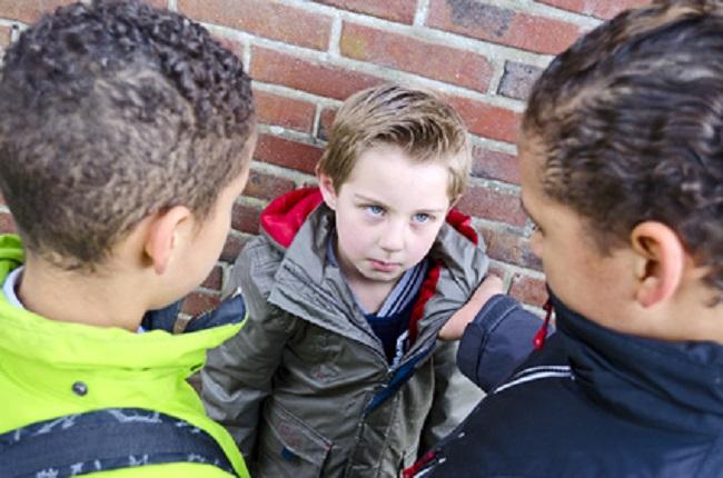garçons en train de harcelé un plus jeune à l'école