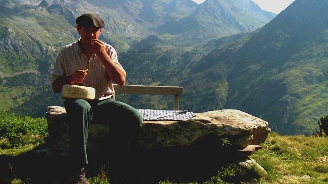 Berger du Béarn en train de manger du fromage de brebis sur un banc en montagne