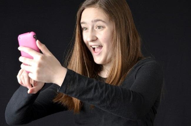 une adolescente se prend en photo avec son smartphone