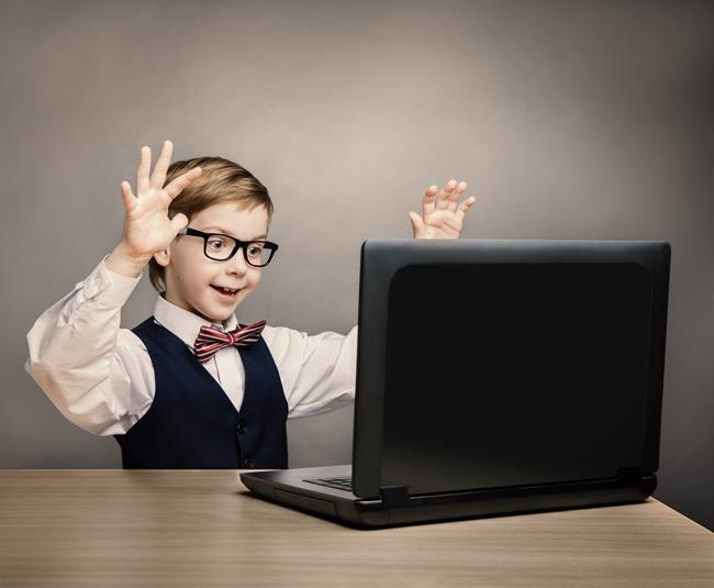 Enfant à lunettes devant un ordinateur portable