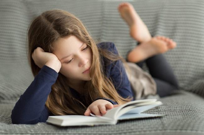 Fillette en train de lire allongée sur le canapé