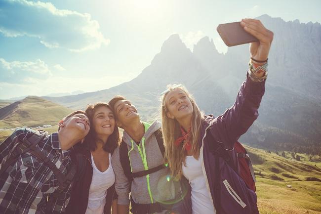 Un groupe d'ado prend un selfie lors d'une randonnée en montagne