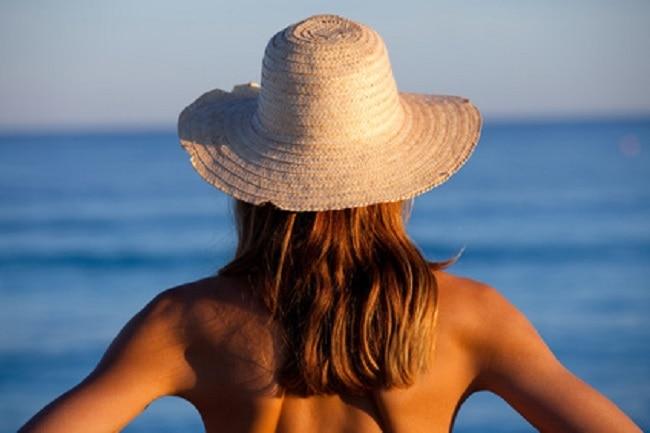 Femme de dos face à la mer, cheveux long, dos nu, bronzée, avec un chapeau de paille