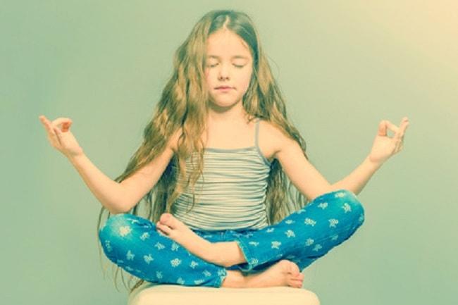 Fillette en train de méditer en position du lotus