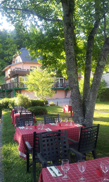 Restaurant extérieur sous les arbres à l'hôtel Les Loges du lac