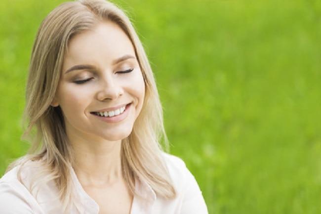 Jeune femme blonde souriante yeux fermés sur fond d'herbe