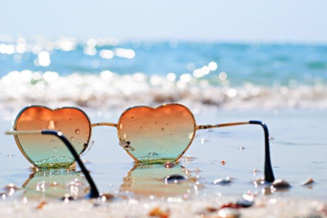 Lunettes de soleil teintées en forme de coeur dans le sable en bord de mer