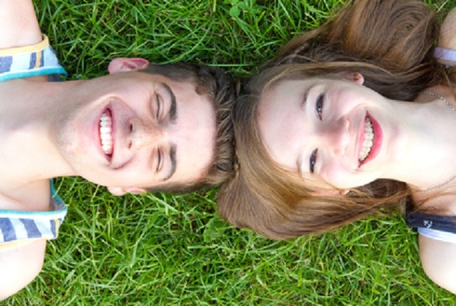 Ados amoureux couchés dans l'herbe