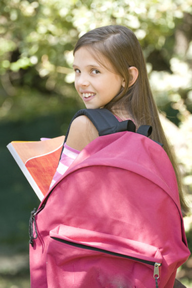 Fillette avec sac à dos rose scolaire