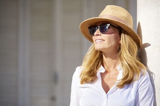 Jeune femme souriante avec lunettes et chapeau de soleil