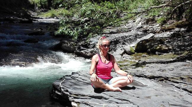 Pause yoga en bord de torrent au cours d'une rando bien-être
