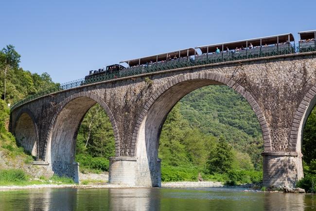 Train de l'Ardèche sur pont de pierre dans les Gorges du Doux