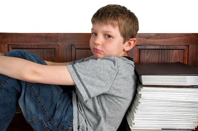 garçon triste assis à côté pile de cahiers