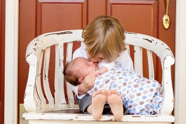 Petit garçon sur un banc embrassant un bébé