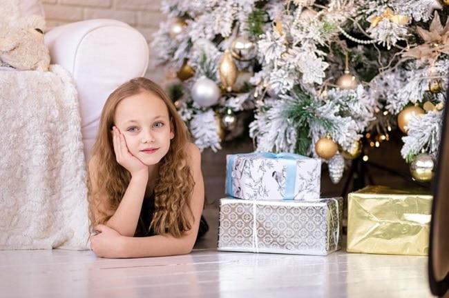petite fille avec ses cadeaux sous le sapin de Noël